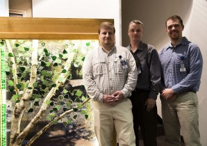 St. Luke's ICU nurses Jeremy Nelson, Pete Boyechko and David Johnson stand next to the Wall of Heroes memorial they created.